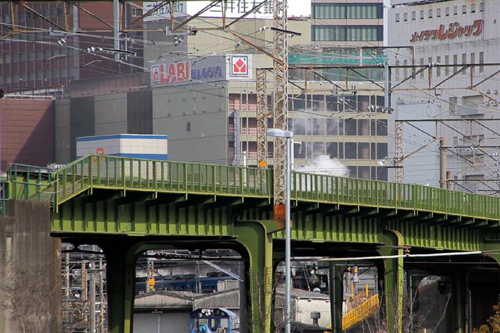 緑の橋脚の間に姿を見せる蒸気機関車
