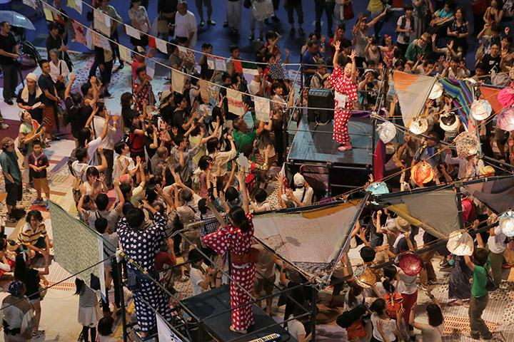 櫓を中心に手をあげて踊る参加者ら